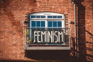black banner on balcony with white text with word feminism