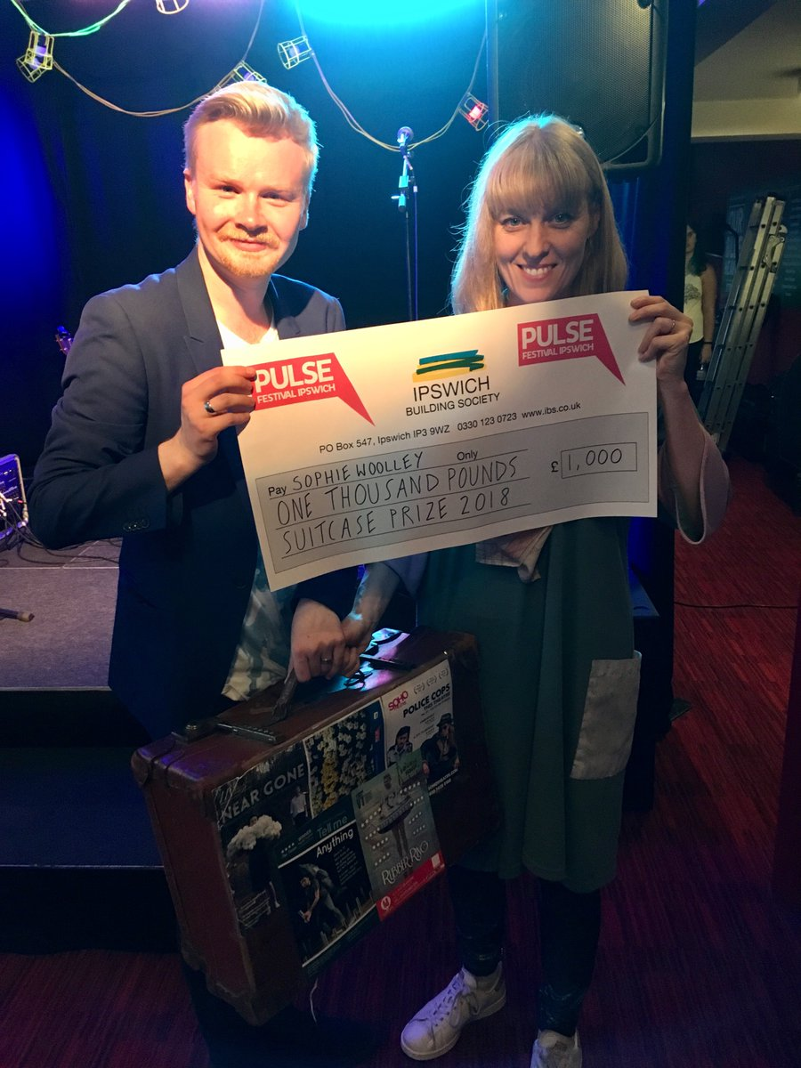 Sophie is handed a giant cheque for one thousand pounds by James McDermott, a white, blond performer with a goatee. He also hands her an old suitcase covered in show flyers.