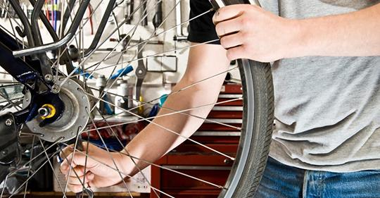 A man's arms and hands hold the spokes of a bicycle wheel in a bike repair workshop.