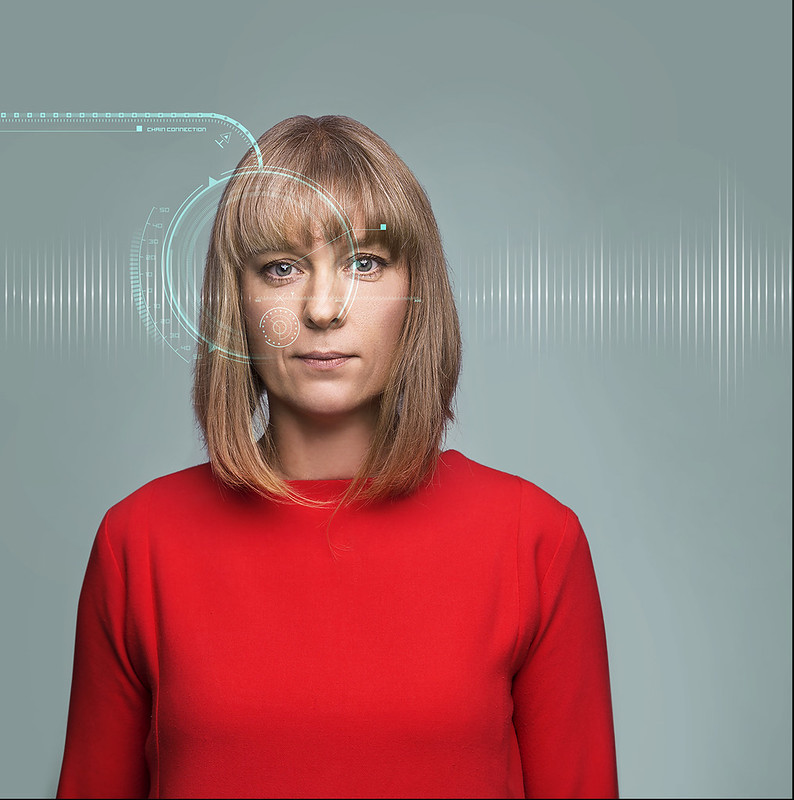 promotional image of sophie woolley Augmented show. She wears a red dress and has a placid enigmatic expression and sound waves zoom onto her head.
