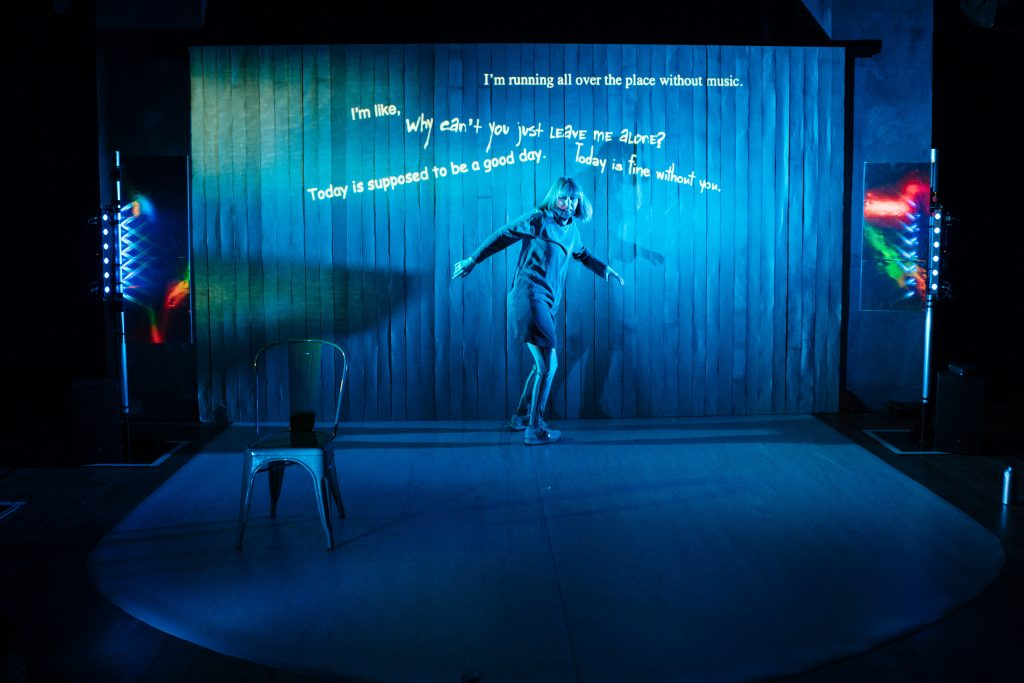 sophie cringes on a blue lit stage as if scared by an unseen enemy. behind her text is projected ,phrases such as 'why cna't you just leave me alone' and 'i'm running all over the place without music'. behind sophie is a slatted curtain. she stands on a lip shaped mat on the stage. there is a simple metal chair and sci fi style lights at the side of the stage. sophie wears a dress silver leggings and has bobbed hair that flies out as she swivels.