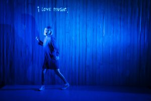 Sophie dances on a blue lit stage, the caption on the slatted curtain behind her says i love music