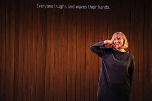 Sophie grins happily and makes a phonecall using her hand in a phone shape. The caption on the gold lit slatted curtain behind her says Everyone laughs and waves their hands.