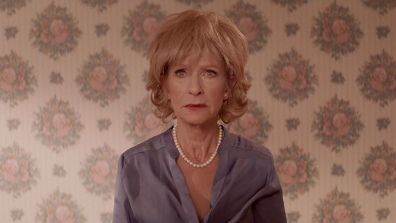 A still from Veneer. Jean St Clair wears a wig and a pensive expression. A white actor with a ginger wig and pearls and a blue blouse in front of retro 1980s wallpaper.
